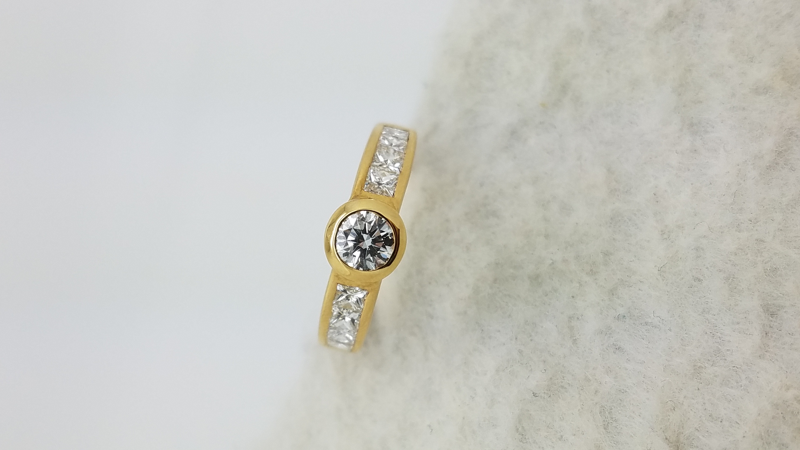 18K	Yellow Gold	Channel band	1.10	ct.	R+PR	Cut	Diamond	H	VS2	Bezel-Set	Solitaire with Accents	Engagement-Ring